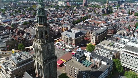 Aerial footage of the Martinitoren also called the St. Martin's Tower is highest church steeple in city of Groningen Netherlands and the bell tower of the Martinikerk als showing Grote Markt 4k