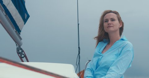 Young adult mid-30s Caucasian female sailing on yacht, bad rainy weather. 4K UHD 60 FPS SLO MO