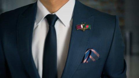 Businessman Walking Towards Camera With Friend Country Flags Pin Qatar - Bangladesh