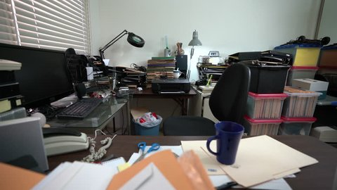 Dolly across messy desk in cluttered office with piles of files and coffee cup.