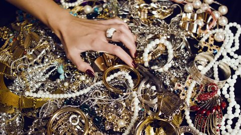 Female hand with a large ring of gold with precious stones touches a pile of gold and silver jewelry on a black background. Luxurious life. Incredible wealth. Hidden treasures.