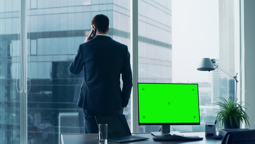 Confident Businessman in His Office Making Phone Call, Personal Computer on His Desk Shows Green Chroma Key Screen. In the Window Panoramic Big City View.