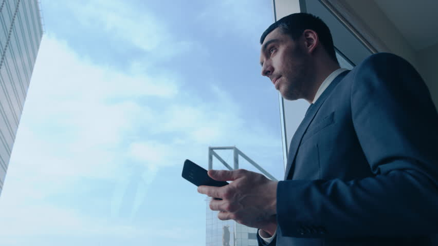 Low Angle Shot of Successful Businessman in a Suit Standing in His Office, Using Mobile Phone while Standing next to Window with Big City View.  #1014231599