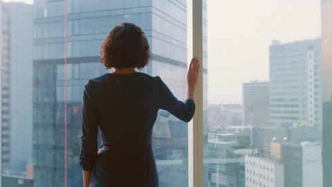 Back View Shot of Successful Businesswoman in the Striking Black Dress Standing in Her Office and Looking out of the Window Thoughtfully.