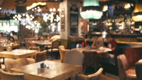 Blurred image of the interior of a large beautiful restaurant with bright lighting. A happy family with a child is sitting at a restaurant at a table, having dinner, talking. Defocussed interior