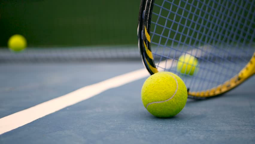 Close up of tennis equipment on the court. Sport, recreation concept. Yellow racket with a tennis ball in motion on a clay green blue court next to the white line with copy space and soft focus. | Shutterstock HD Video #1014243899