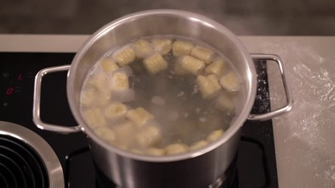4K cooking footage, top view close up gnocchi approaching surfase of scalding water in pot on induction cooktop
