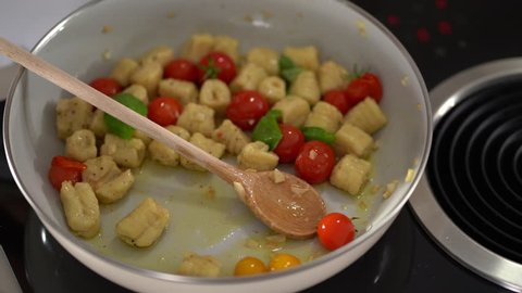 4K cooking footage, close up fresh potato gnocchis with tomatos in pan olive oil wooden spoon putting green basil stiring all together