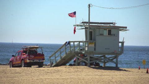 Venice Beach, California / USA - September 9th, 2016: Lifeguard Tower with Tourists and Locals at Venice Beach With Ocean Waves Surf.