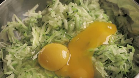 CLOSE UP FOOD: yolk falling downt ot gratted zucchini into a metal bowl