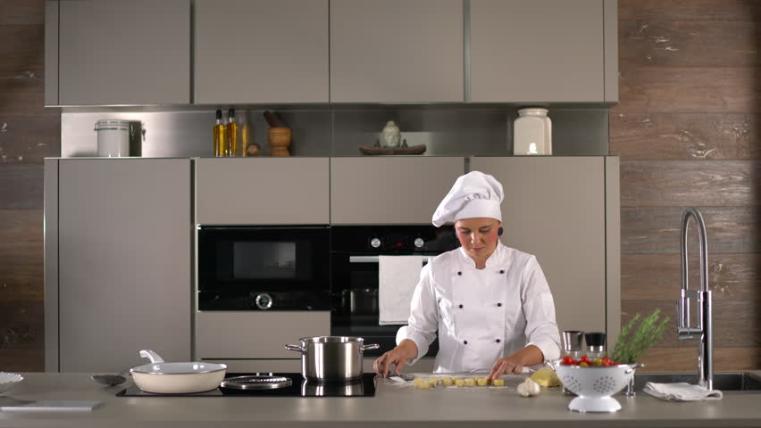 4K cooking footage, woman in cooking dress female cook preparing dough for fresh gnocchi in kitchen wideangle