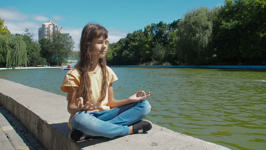 A child meditates in nature. A little girl in a lotus pose by the pond in the park. | Shutterstock HD Video #1014317369