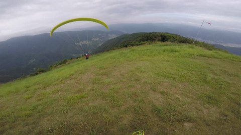 Solo Paraglider sets up glider on top of a mountain in Japan in Summer