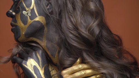 Woman model in black gold obi art hugs herself and looks at camera, close up