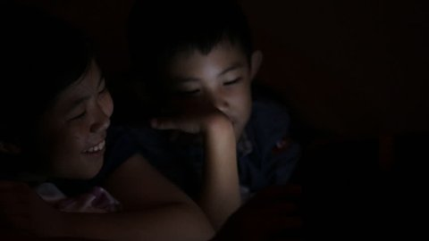Close up face and hands asian little boy and girl playing computer games lying in his bed in evening. Child using tablet smartphone.