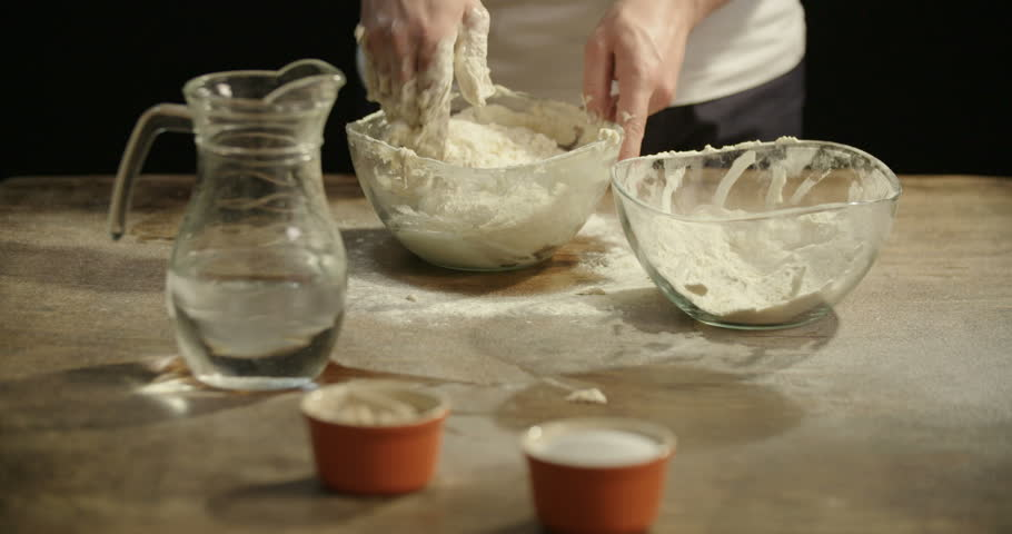 Caucasian man kneading dough in a clear glass bowl on a table dusted with flour. | Shutterstock HD Video #1014350999