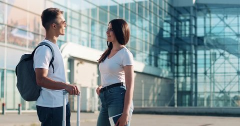 Attractive couple in love, saying goodbye near airpotr or train station. Concept of departure, farewell, business trip. Summer time, sunset