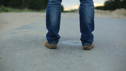a man pees on the asphalt country highway. male legs in jeans and brown shoes.