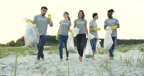 Group of young multiethnical people walking the beach with plastic bags full of garbage. Environment volunteering.
