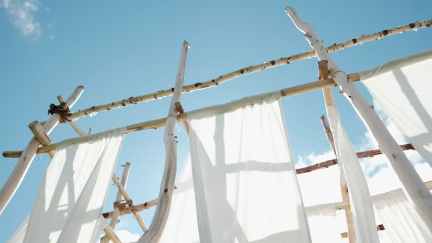 White linen cloth on wooden poles swings in the wind. Against the blue sky and green trees and fields. | Shutterstock HD Video #1014364169