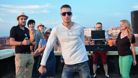 Active European man in sunglasses having fun dancing in the middle of dance floor at rooftop party