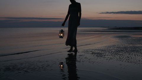 Girl in dress walking on beach and holding old kerosene lantern in her hand after sunset at night