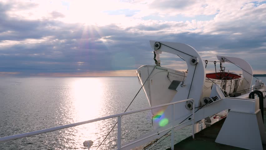A lifeboat on a cruise ship with an amazing sunset on a calm ocean
