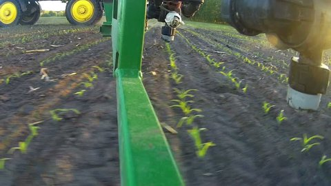 A view of the spray nozzle while working in the field. Sprayer nozzle in operation, tractor sprayer works in the field.