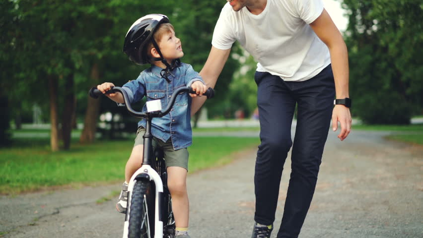Slow motion of loving dad teaching his adorable son to ride bicycle in park holding bike and talking to child. Fatherhood, childhood and active lifestyle concept. | Shutterstock HD Video #1014435359