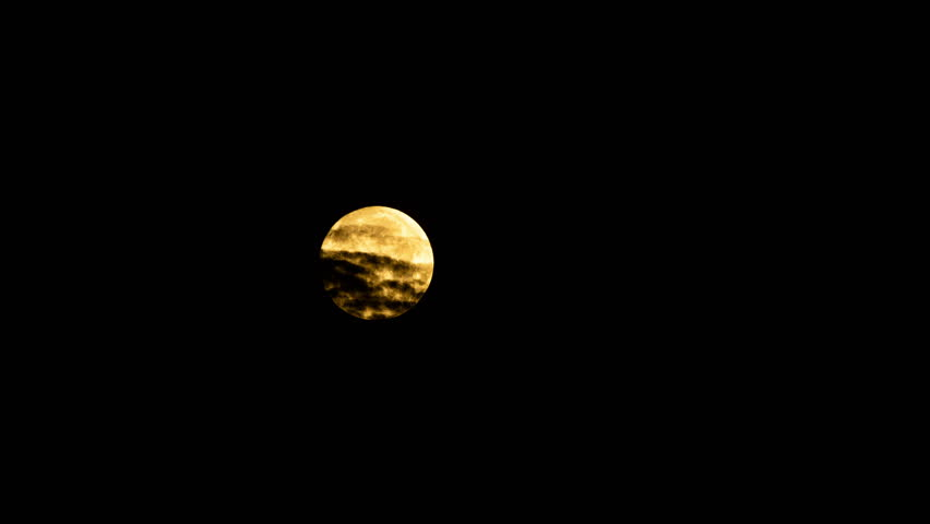4k time lapse of the full moon passing behind clouds at night
