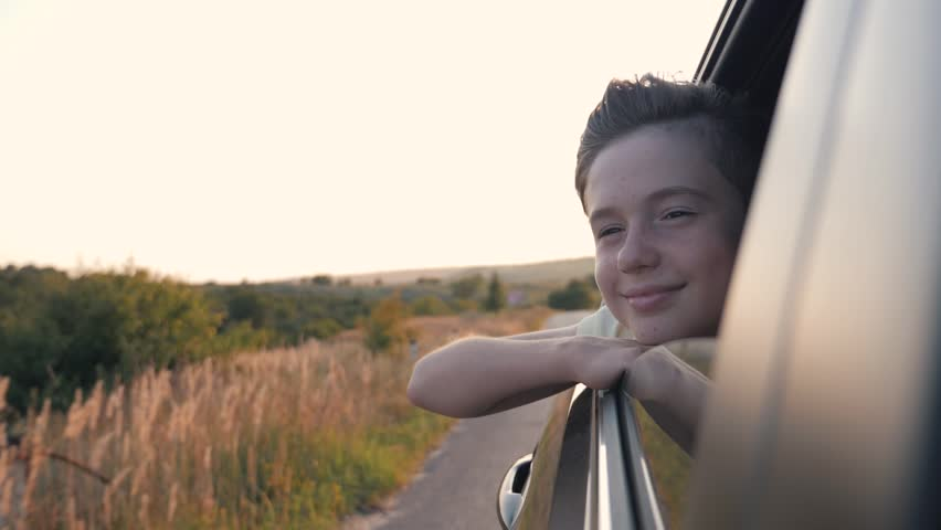 Teen boy looking out the car window. Summer trip with family