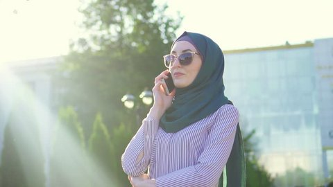 Young stylish attractive muslim woman in hijab and glasses talking on the phone,sunflare.Slow mo