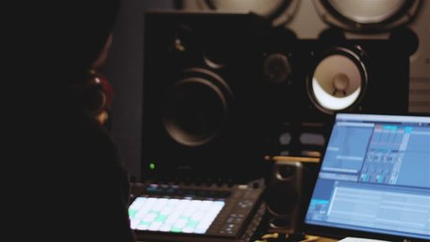 Music producer/audio engineer working in front of the computer on track while raising hands and enjoying as he listens