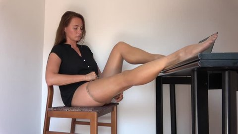 woman sitting on bed  massaging beautiful  long legs in pantyhose