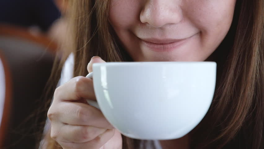 An Asian woman enjoy drinking hot coffee with feeling good in cafe