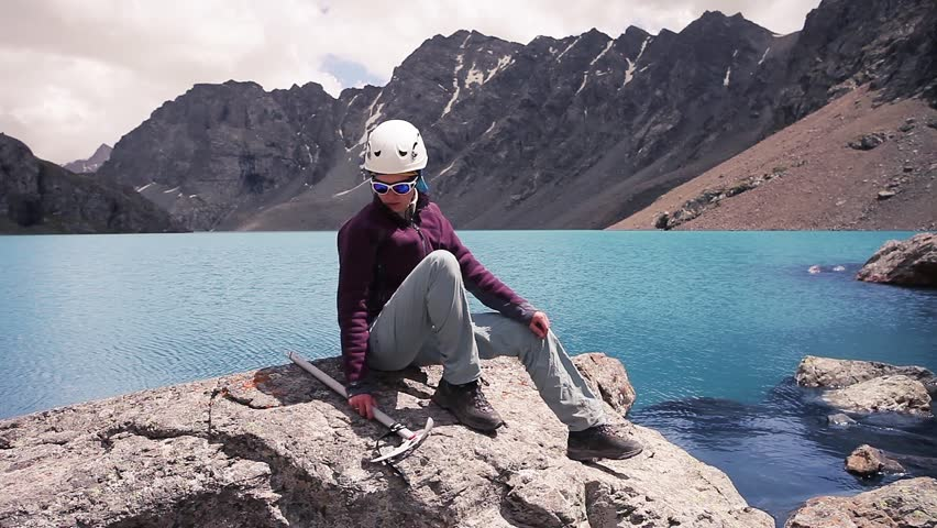 Pretty Climber Girl on mountains lake Ala-Kul. Looping movie. Cinemagraph.