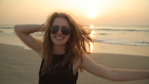 A young sexy blonde girl in a short black dress and glasses walks along the ocean shore at sunset smiling playfully looking at the camera and correcting her hairstyle. Stabilised following camera.