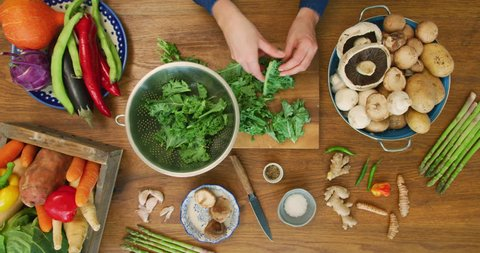 Overhead view of female's hands plucking kale from their stalks in colander . Lockdown shot of woman is preparing leaf vegetable in kitchen. Various nutritious food are on table. Shot on RED Camera.