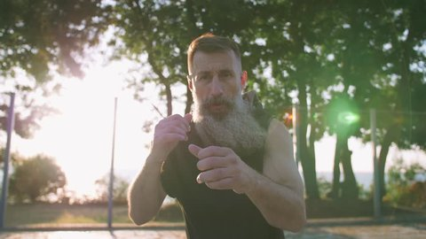 Middle aged man with long gray beard boxing with shadow on basketball court during sunrise, slow motion
