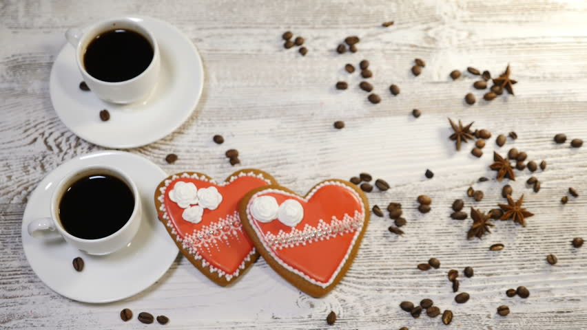 Food art. Broken heart concept. 2 cups of freshbrewed coffee and 2 heartshaped Gingerbread Cookies placed on wooden background with coffee beans around. Female hands take a cookie and break it