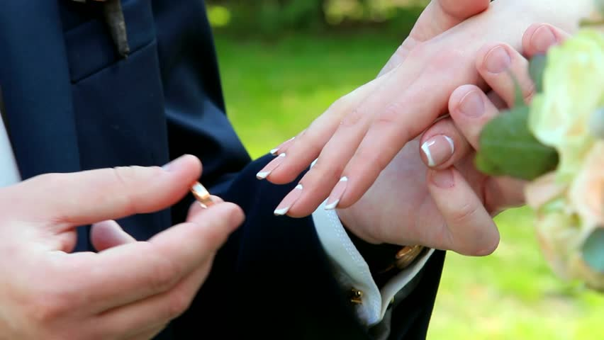 gold wedding rings and hands of just married couple of bride and groom people get