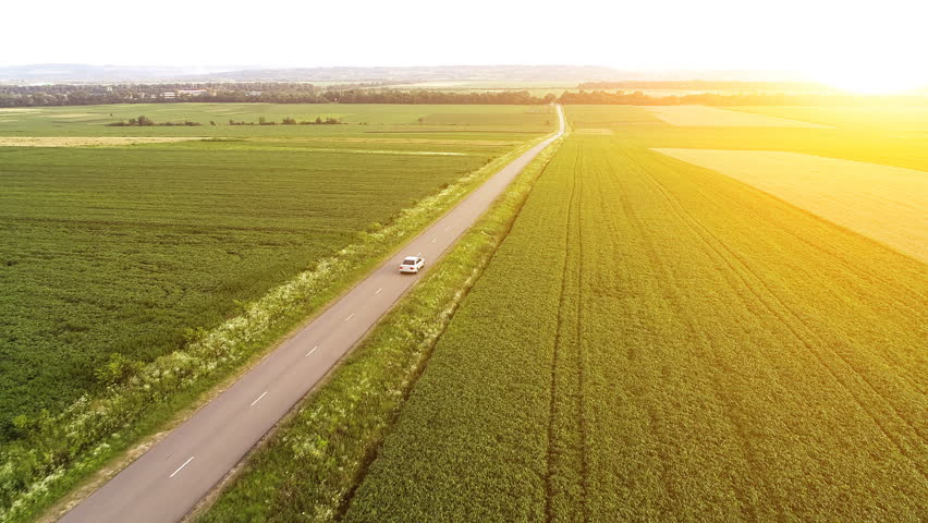 The flight above the beautiful field with a road. quadcopter shot | Shutterstock HD Video #1014587939