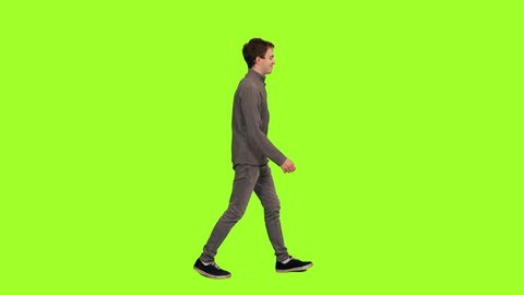 Young handsome caucasian man in casual wear walking on green chroma key background, Side view, 4k pre-keyed footage