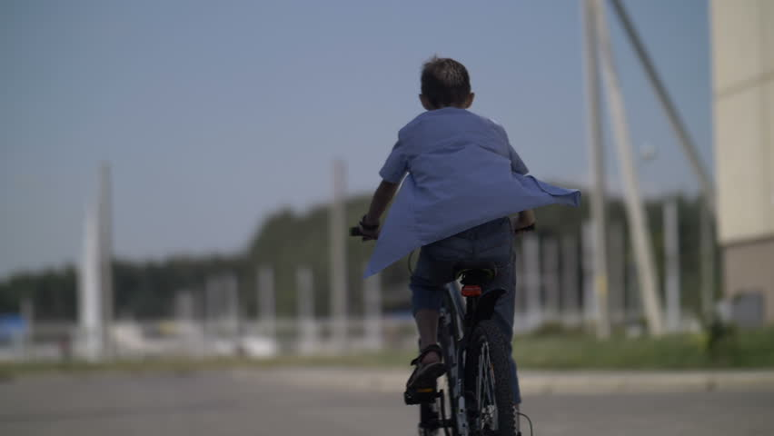 Boy is riding a bicycle, back view, shirt is developed in the wind, slow motion | Shutterstock HD Video #1014612929
