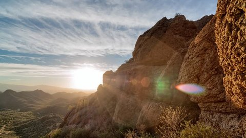 Timelapse of a partly cloudy desert sunrise viewed from a mountain pass.  Shot in HDR.  Includes hyperlapse panning motion past rocks in the foreground.