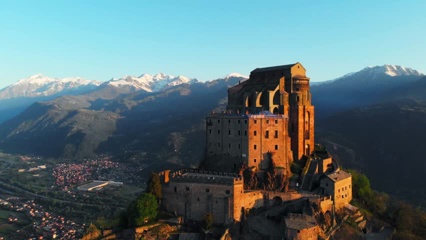 Aerial: drone flying at old medieval abbey perched on mountain top, stunning background of the snowy Alps at sunrise. Sacra di San Michele (italian) - Saint Michel Abbey (english traslation) - Turin,