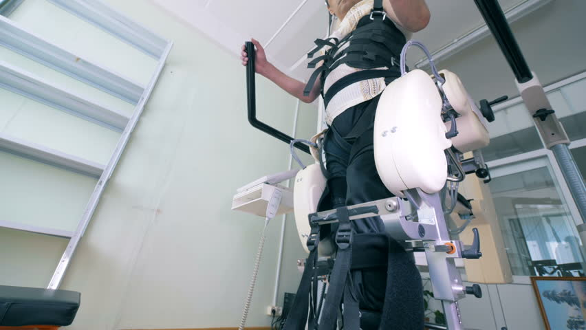 Male patient with physical impairments is exercising on a walking track simulator. Electronic medical robotic for rehabilitation.