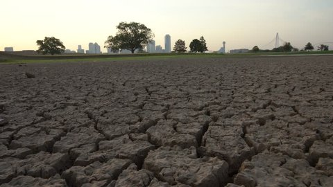 Dry lake bed cracks w/ modern city in background during drought w/slider movement
