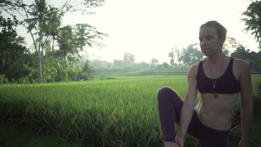 Girl practice extended hand to big toe yoga pose at rice field rapid slow motion
