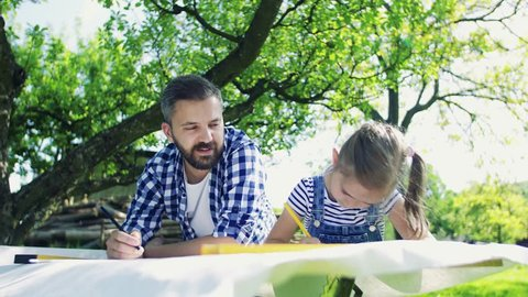 Father with a small daughter outside, planning a wooden birdhouse.